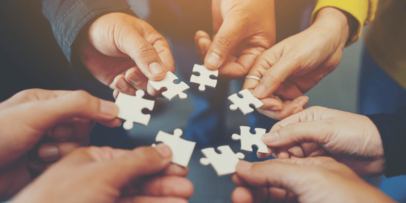 Team hands, each with a puzzle piece.